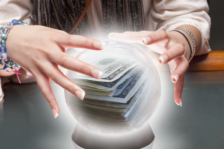 Mixed race fortune teller with crystal ball with money inside