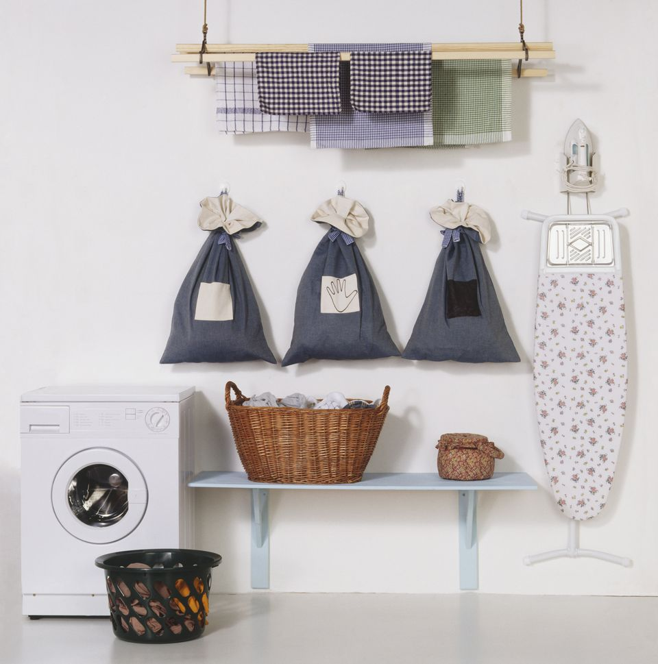 Washing machine, laundry bags fixed to wall, hanging rail, ironing board and wicker baskets containing clothing, front view.