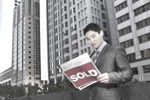 Asian man reading a real estate magazine