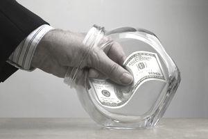 Man taking 100 dollar bill from jar, close-up of hand