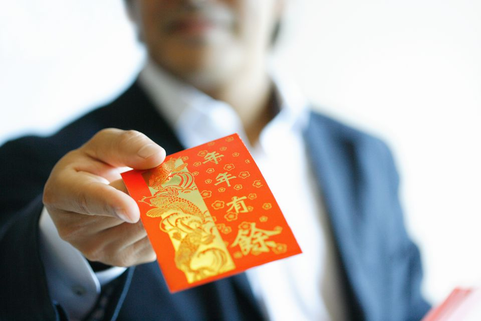 man holding a Chinese red envelope
