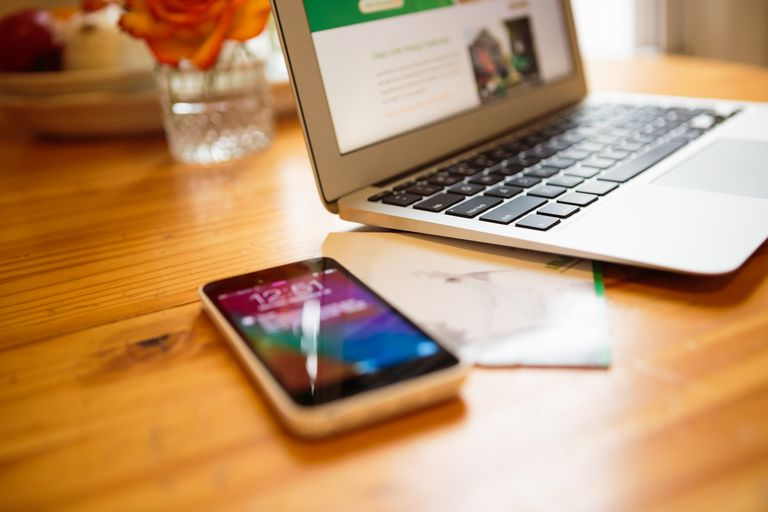 Smartphone and laptop on kitchen table