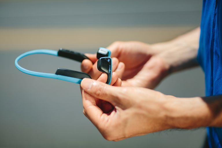 The Trekz Titanium Mini bone conduction headphones held in hands