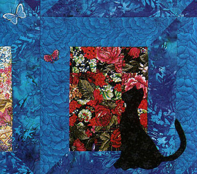 Needleturn appliqué cats and butterflies on a patchwork quilt.