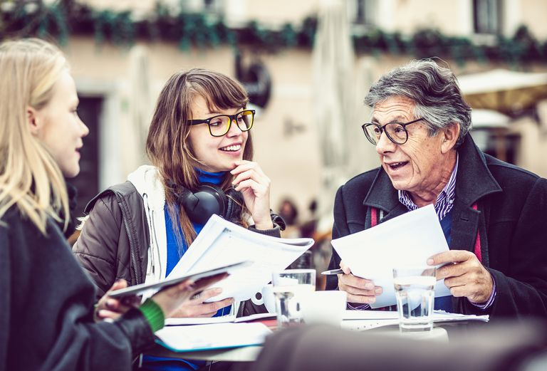 Man and two women looking at paperwork at table