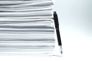 pen leaning against stack of documents