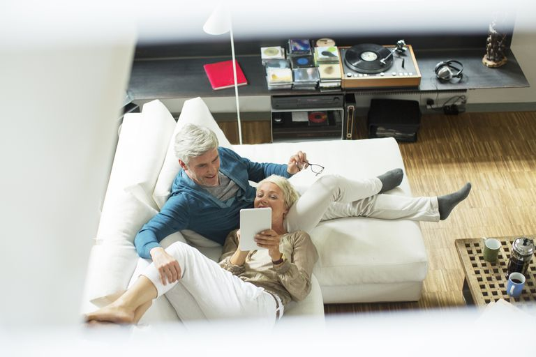 Mature couple relaxing on sofa and looking at tablet