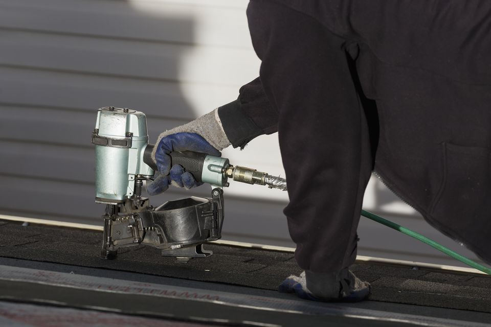 Close up of air nailer, with male roofer nailing new shingles