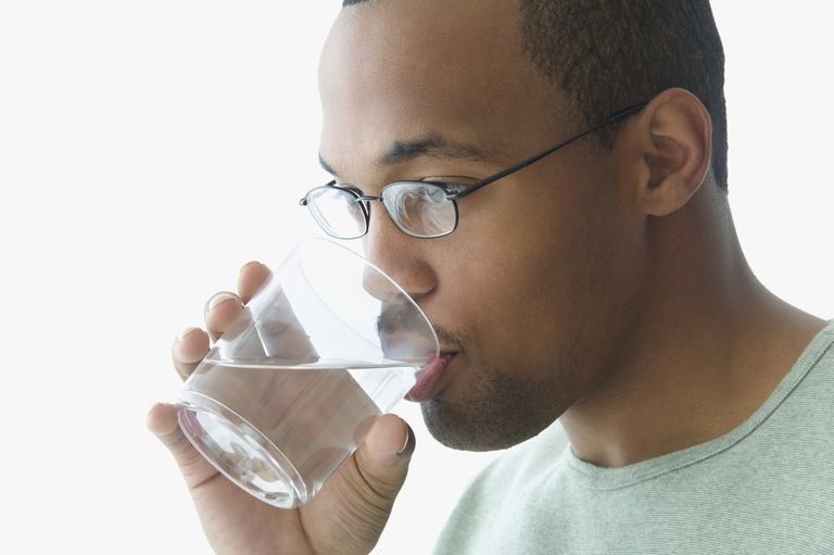 College man drinking water to stay hydrated.