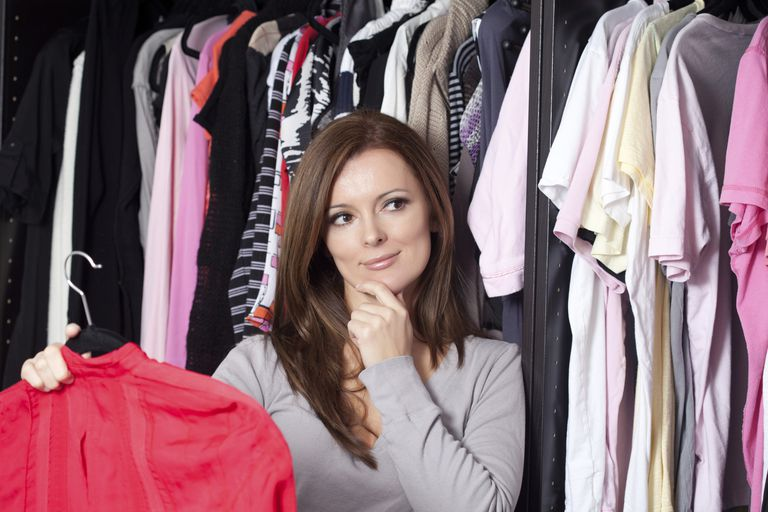 A woman stands near her closet and thinks about what to wear.