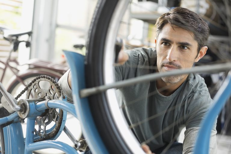 Man repairing bicycles tire in shop
