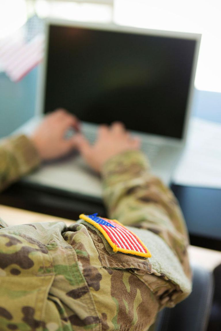 American Soldier in uniform typing on laptop.