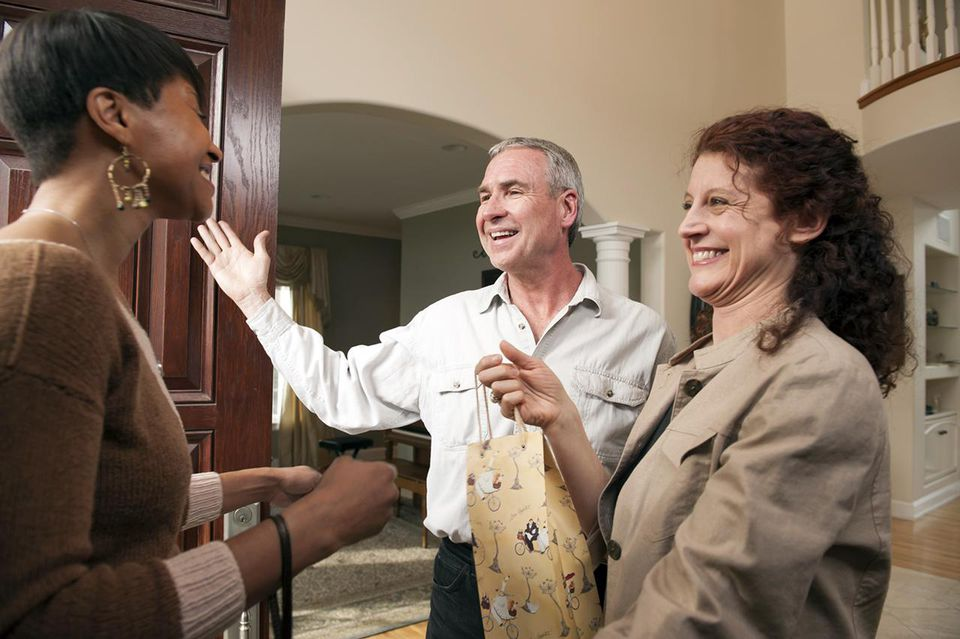 Woman guest being greeted at front door by host couple