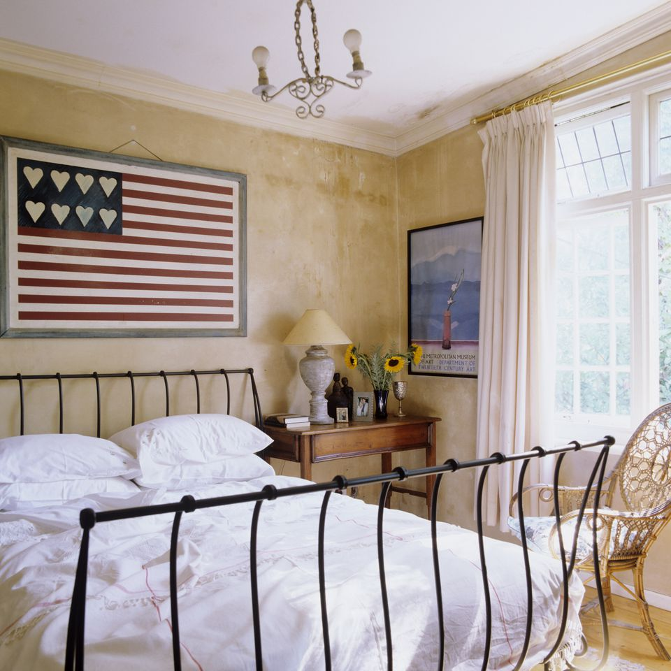 Cottage bedroom with iron bed and flag wall hanging.