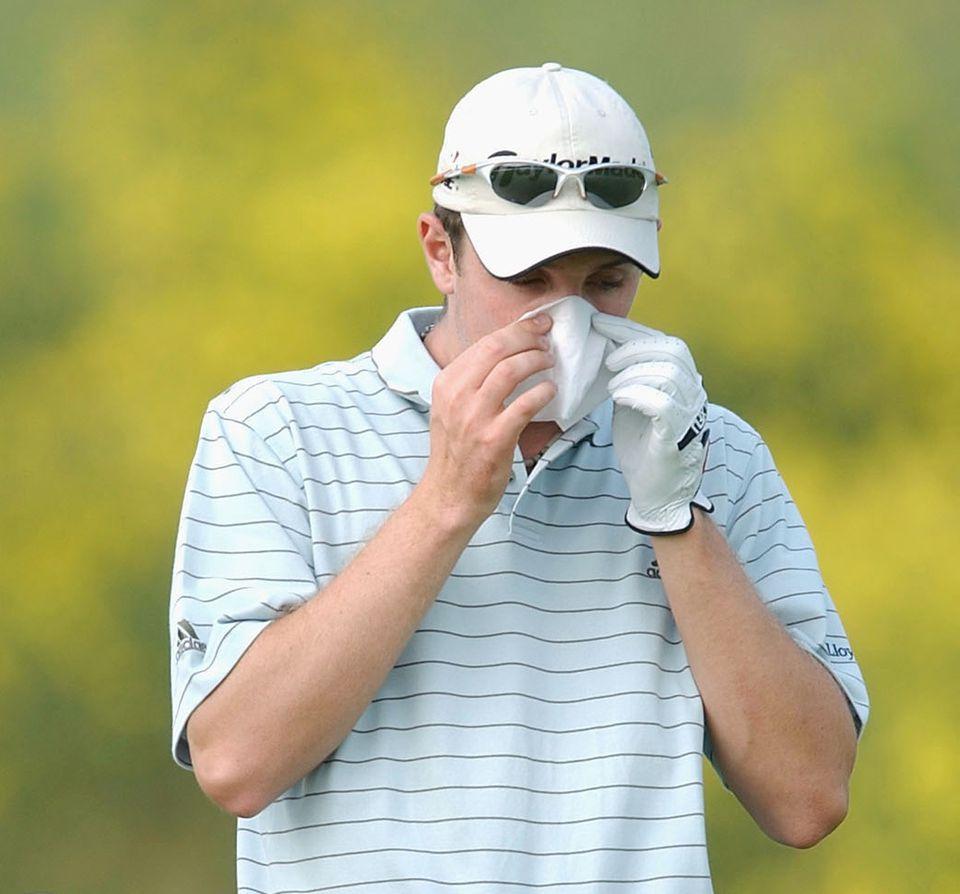 A golfer sneezing into a handkerchief