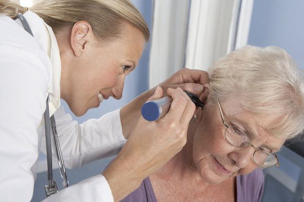 Female doctor examines an elderly woman's ear