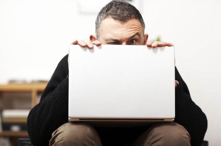 Man making faces from behind laptop