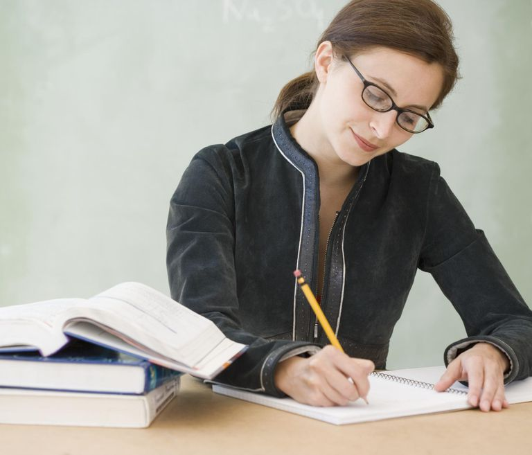 Woman writing in notebook at school, front view.