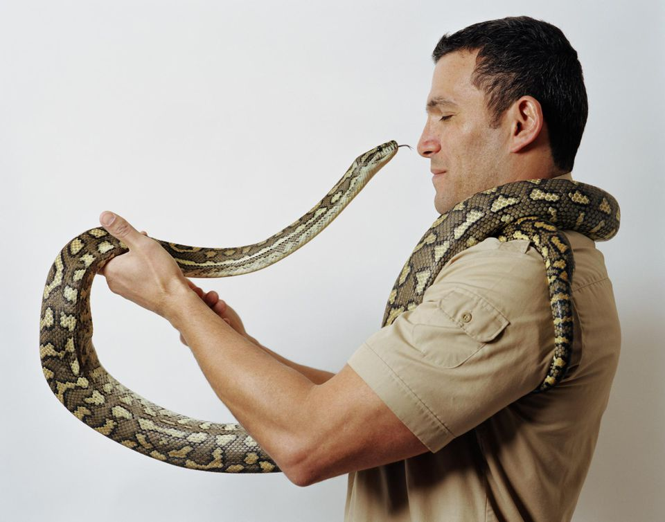 Man holding snake in front of face, eyes closed, profile
