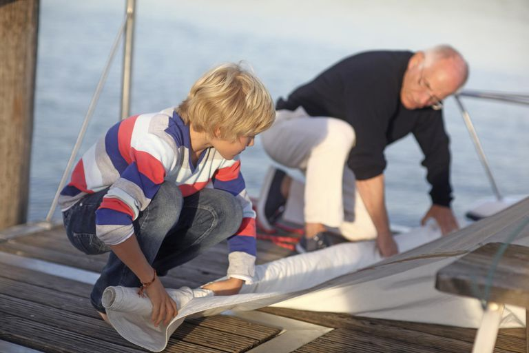 Grandson and grandfather rolling sail on harbor jetty