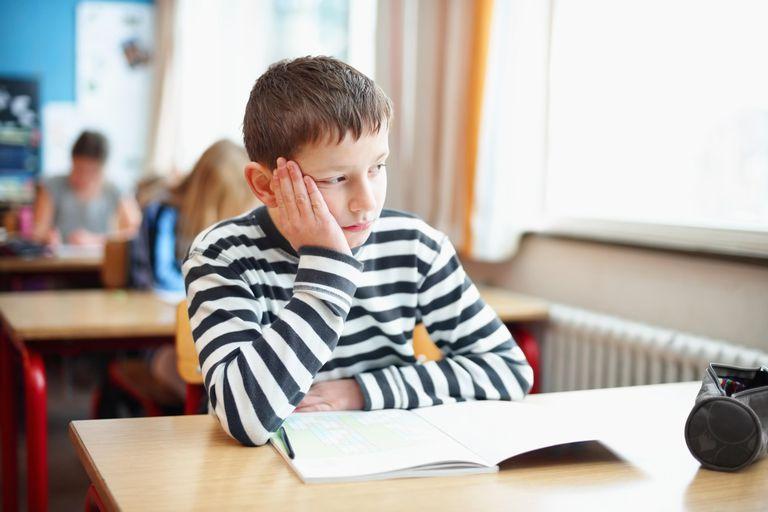 Bored little school boy in the classroom