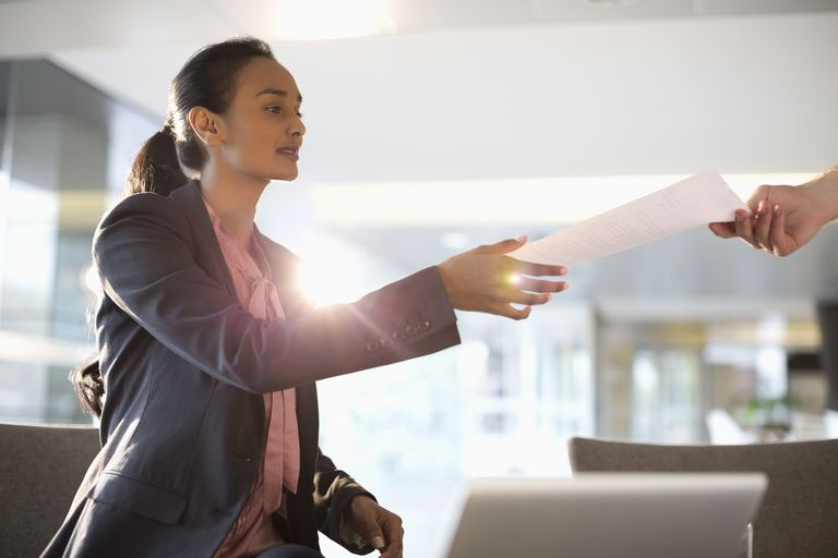 Businesswoman reaching for paperwork