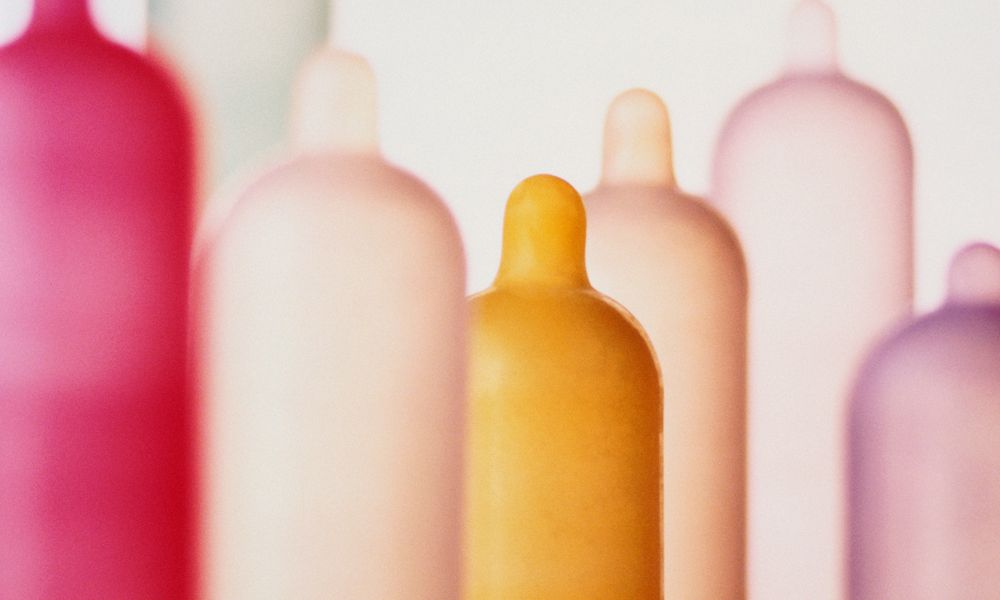 Different coloured condoms on tubes