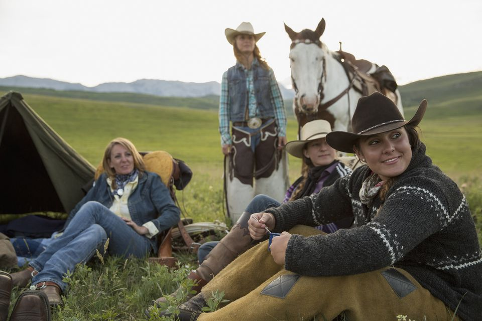 Female ranchers relaxing at campsite in remote field