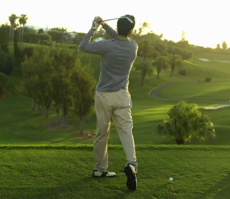 Young man on golf course practicing drive, rear view Details