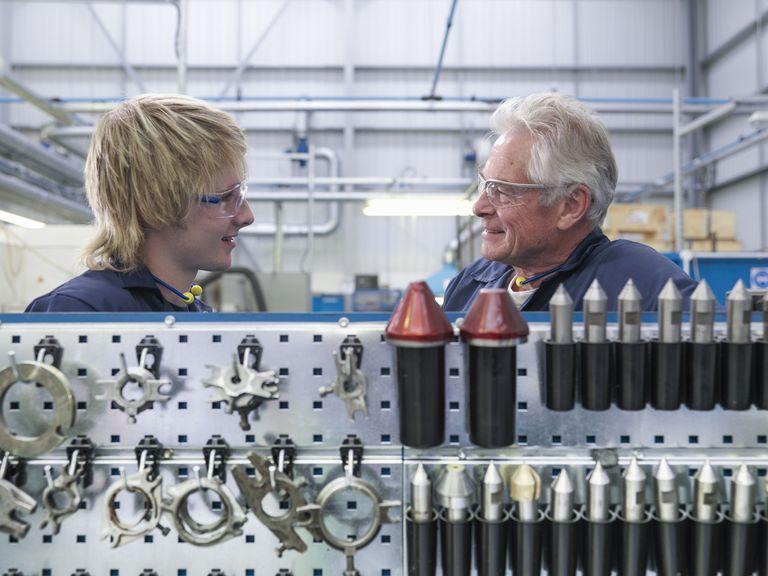 Senior engineer instructing apprentice in factory