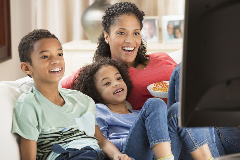 family watching tv. mixed race family watching television together tv
