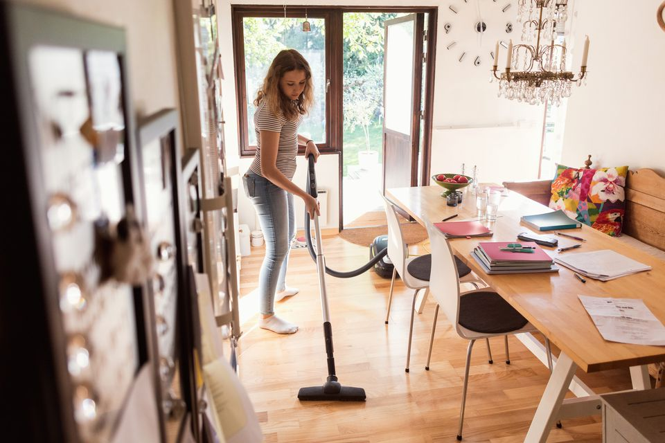 Full length of teenage girl cleaning hardwood floor with vacuum cleaner at home