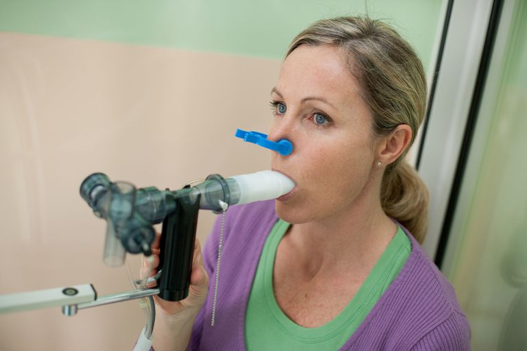 Spirometry Woman undergoing a lung function test using a spirometer that measures the maximum rate at which air is expelled from the lungs, Respiratory diseases department, Limoges hospital, France.