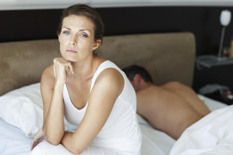 Women Awake in Bed Beside Sleeping Man