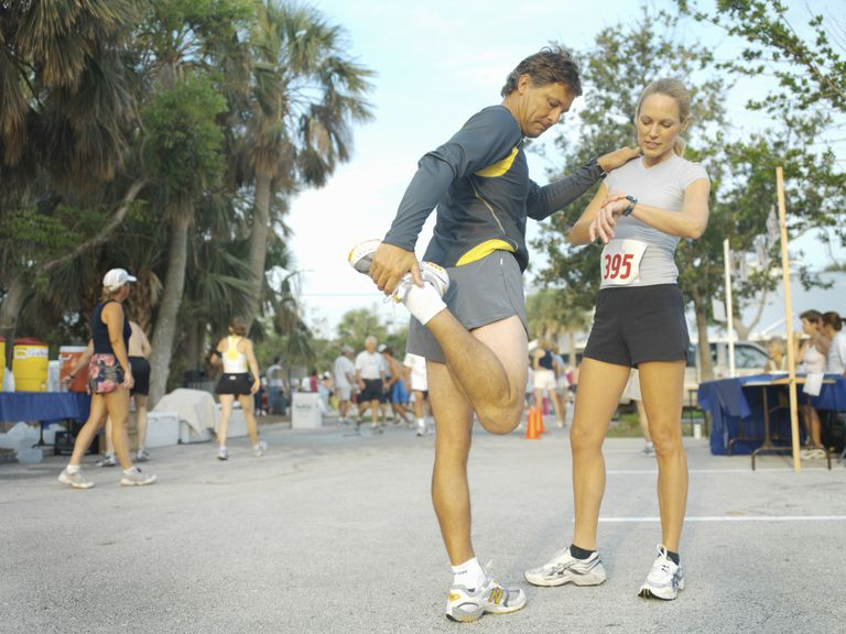 man stretching legs and woman checking watch before marathon