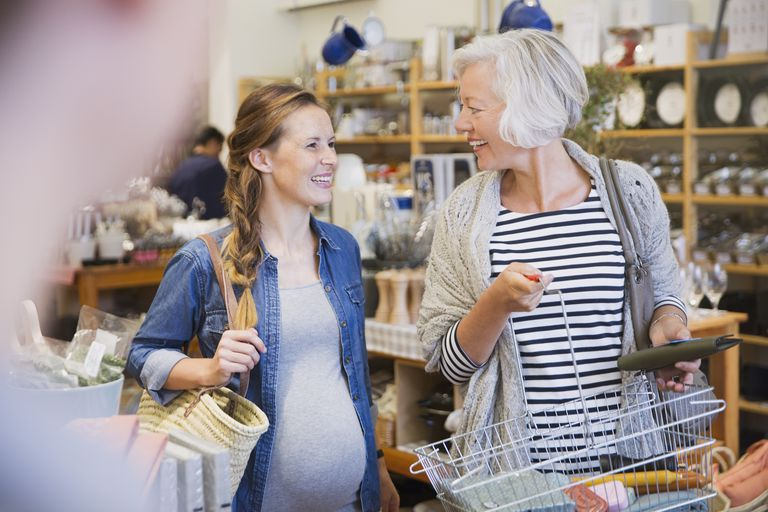 Smiling pregnant woman and mother shopping in shop
