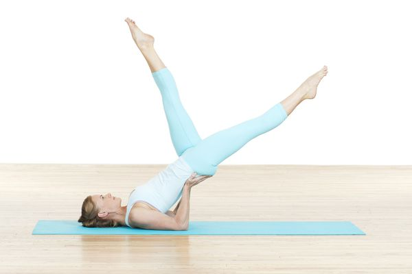 Woman practising Scissors Pilates mat exercise, side view