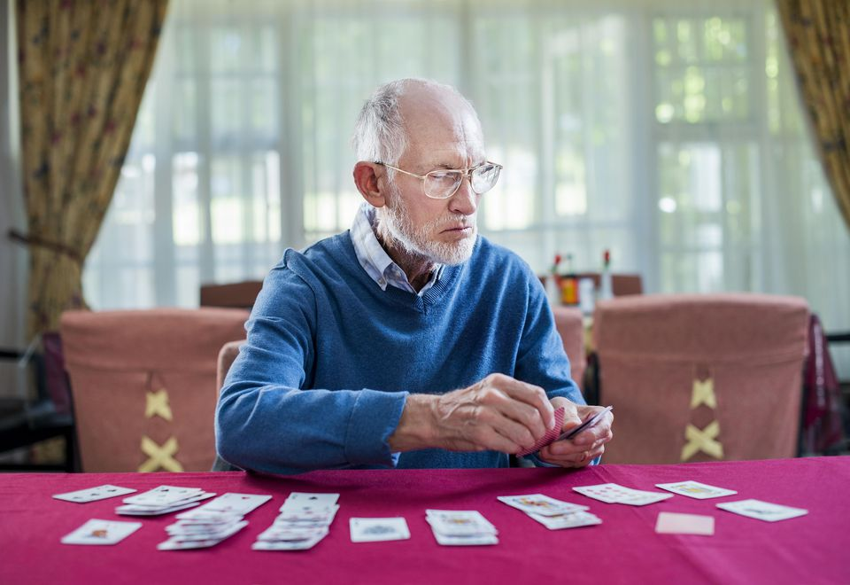 Senior man playing cards in nursing home