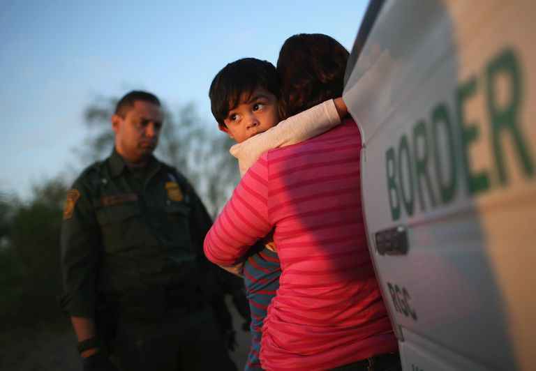 Illegal immigrant mother hugs child while being questioned by US Border Patrol agents