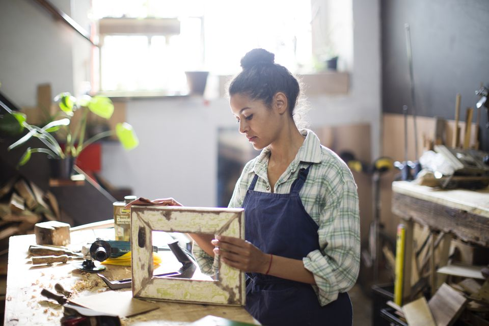 Woman using sandpaper to restore wooden frame