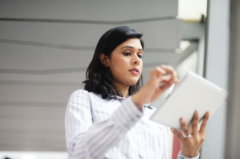 Indian-Singaporean business woman using a tablet
