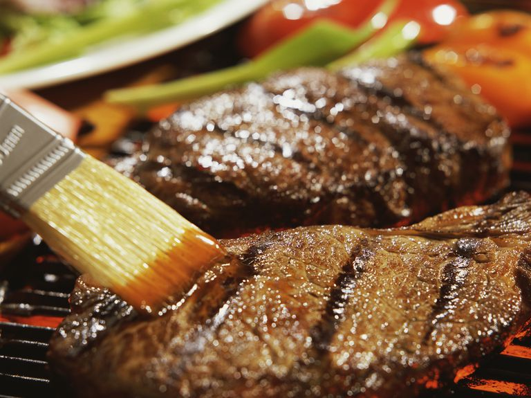 steak on grill being brushed with sauce