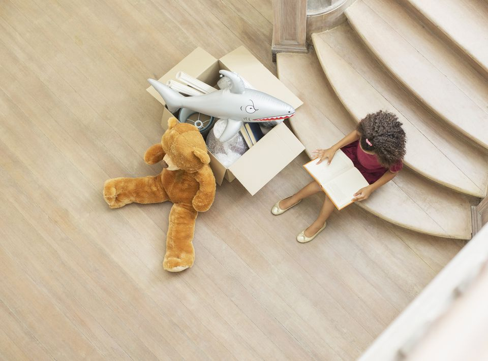 Young girl reading on stairs with toys