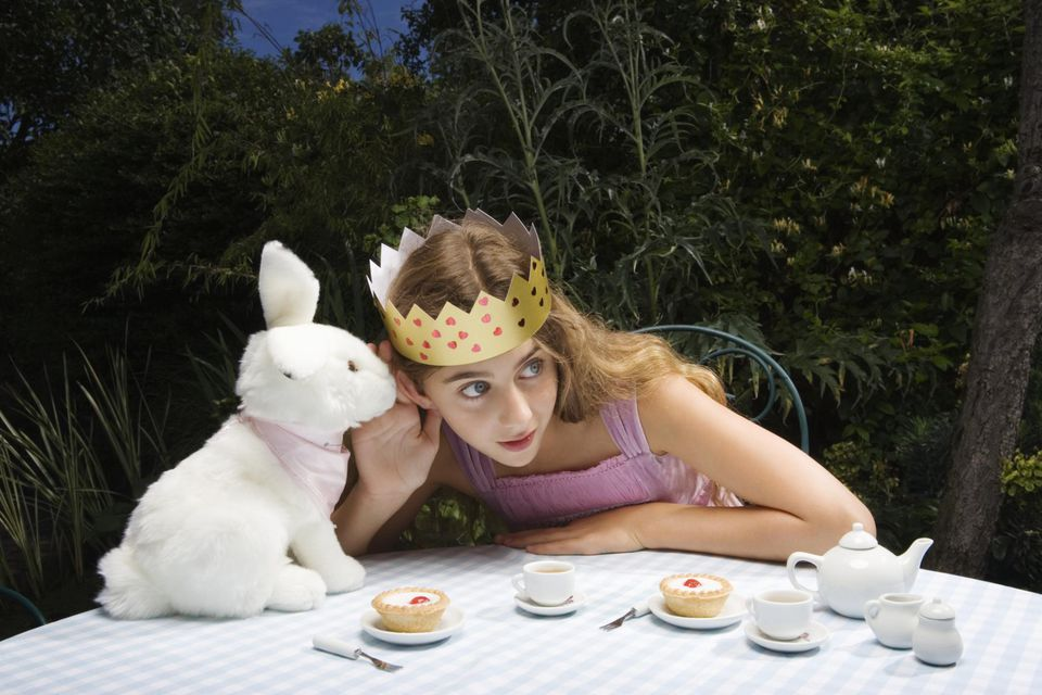 Girl (10-11) wearing crown having tea party with toy rabbit