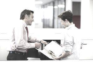 Businessman training teenage boy in office