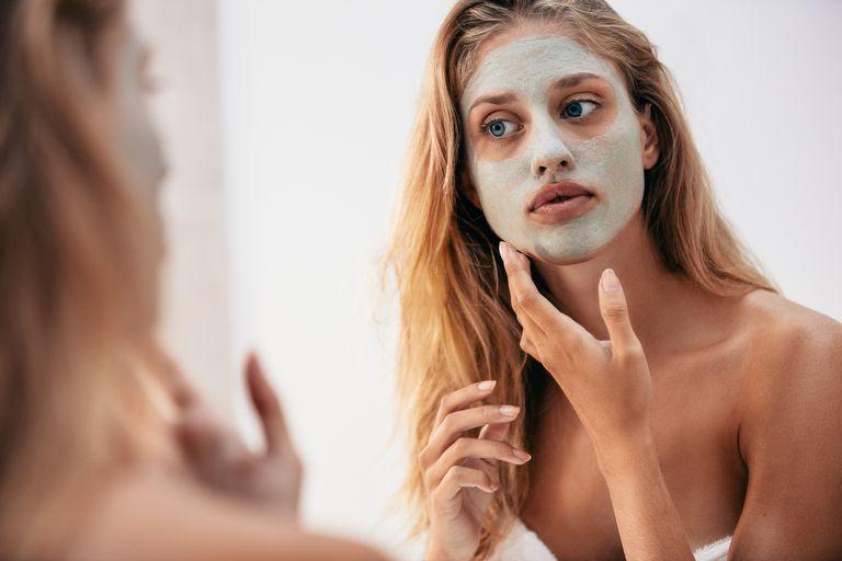 woman applying mask in mirror