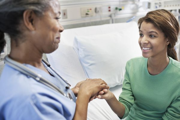 Doctor and patient holding hands in hospital