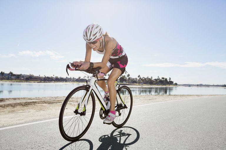 Female triathlete riding bicycle on street
