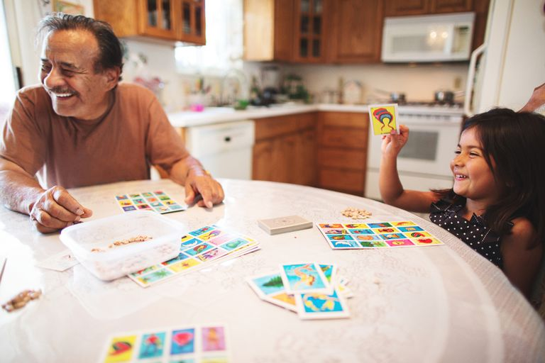 Little girl playing board game with grandfather