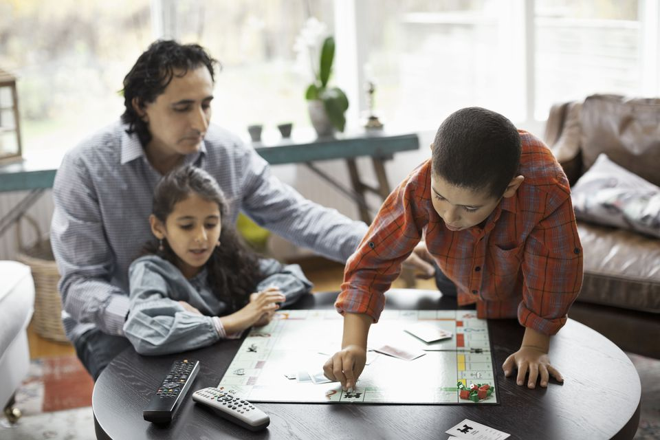 Father and children playing monopoly game in living room